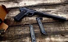 Черный пистолет с глушителем, обоймы к пистолету