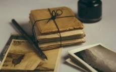 Чернильница, чернильная ручка, старые фоторгафии, стопка писем