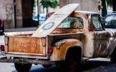 Старый, ржавый пикап форд с доской для серфинга