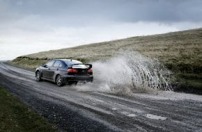 Mitsubishi Lancer Evolution едет по мокрой грунтовке