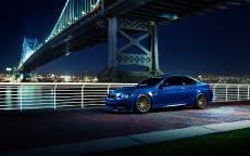 Синий БМВ едет по ночной набережной
