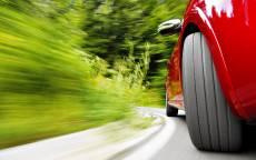 Красная машина на скорости входит в поворот