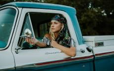 Девушка смотрит в зеркало заднего вида автомобиля, пикап