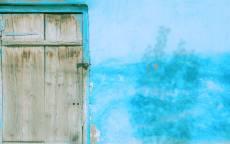 голубая стена дома с деревянной дверью
