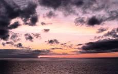 черные облака на море, на фоне розового неба