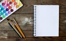 Краски, кисти, блокнот, деревянный стол, художник