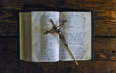 Распятие лежит на библии, деревянный стол