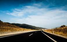 Дорога, поворот, холмы, черный асфальт, забор, разметка, облака, небо