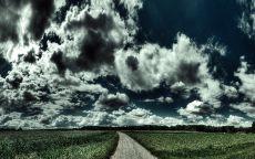 Дорога в поле под облаками