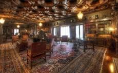 Домашняя библиотека со старинной мебелью и ковром на полу