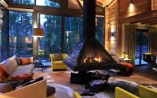 Каминная комната в деревянном доме со стеклянной стеной