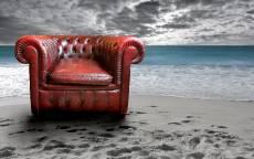 Старое красное кожное кресло на пляже