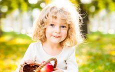 Ребенок с корзинкой спелых яблок