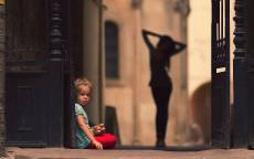 Девочка с игрушкой на улице на фоне силуэта девушки