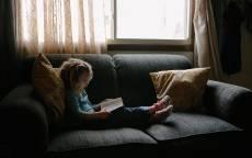 Окно, диван, подушки, ребенок читает книгу
