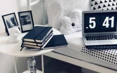Ноутбук, книги, фотографии в спальне