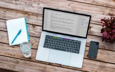 Ноутбук и смартфон лежат на деревянном столе