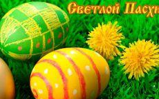 Пасхальные яйца и одуванчики на зеленой траве