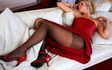 Девушка в красном платье лежит на кровати.