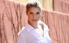 Девушка в белой блузке стоит у розовой стены дома
