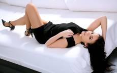 Брюнетка в черном платье лежит на белой кровати