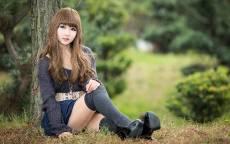 Китаянка в чулках сидит в лесу у дерева