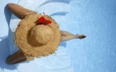 Девушка в соломенной шляпе сидит на краю бассейна