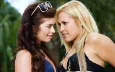 Девушки блондинка и брюнетка смотрят в глаза друг другу
