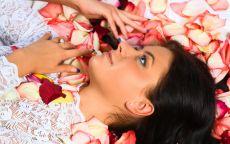 Девушка лежит в лепестках роз