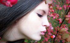 Девушка дует на цветок