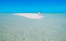 Девушка на песчаной косе голубого океана.