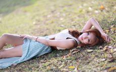 Красивая китаянка лежит на земле.