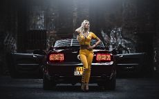 Девушка в желтом у черного автомобиля.