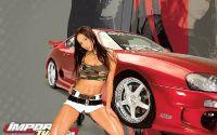 Девушка сидит у красного автомобиля
