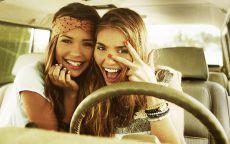 Две молодые девушки за рулем автомобиля.