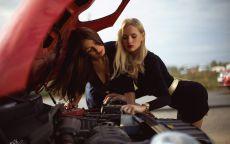 Брюнетка и блондинка осматривают двигатель автомобиля.