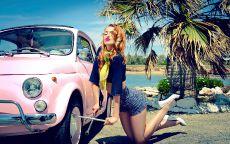 Рыжая девушка у розового автомобиля.