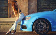 Девушка сидит на капоте голубой машины.