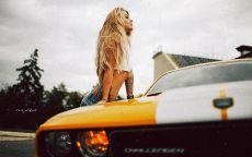 Блондинка облокотилась на капот автомобиля.