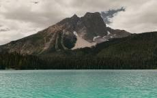 озеро с голубой водой на берегу леса в горах