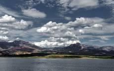 Облака, горы, зеленый берег, озеро