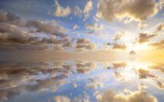 Облака зеркально отражаются в воде.