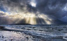 Лучи солнца пробивают облака над морем.