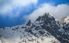 Белый снег на серой стене горы