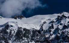 Горы, скалы, снег, темное небо, ели