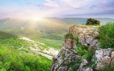 Солнце восходит над горной долиной.