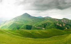 Зеленые холмы под дождевой тучей.