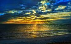 Лучи солнца пробиваются сквозь облака над морем.