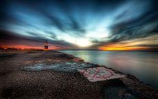 Маяк на берегу вечернего моря.