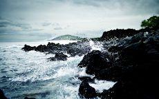 Волны разбиваются о камни на берегу.